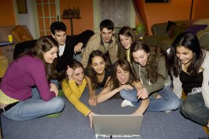Friends looking at laptop on rug in living room, laughing